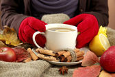Hands holding cup of hot drink and autumn leaves, on burlap background — Stock Photo