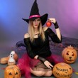 Halloween witch with red apple on color background — Stock Photo