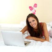 молодая красивая женщина с ноутбуком в постели — Стоковое фото