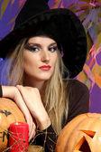 Halloween heks met pumpkins op kleur achtergrond — Stockfoto