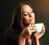 Beautiful young woman with cup of coffee, on brown background — Stock Photo