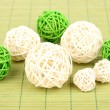 Wicker bamboo balls on bamboo mat - Stock Photo