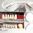 Stock Photo: Set of dental tools with denture on grey background