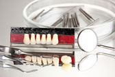 Set of dental tools with denture on grey background — Stock Photo