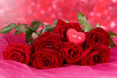 Beautiful bouquet of roses on pink fabric on red background — Stock Photo
