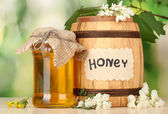 Sweet honey in barrel and jar with flowers on wooden table on green backgro — Stock Photo