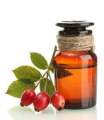 Medicine bottle with hip roses, isolated on white — Stock Photo