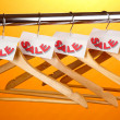 Wooden clothes hangers as sale symbol on orange background - Stockfoto