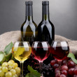 Bottles and glasses of wine and grapes on grey background — Stock Photo #14033536