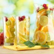 Jar and glasses with citrus fruits and raspberries, on green background - Foto de Stock