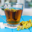 Stock Photo: Cup of tewith immortelle on blue wooden table on window background