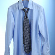 Shirt with tie on wooden hanger on blue background — Stockfoto