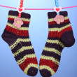 Pair of knit striped socks hanging to dry over blue background — Stock Photo