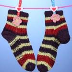 par de tricotar meias listradas pendurado para secar sobre fundo azul — Foto Stock #14034684