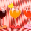 Stock Photo: Colorful cocktails with bright decor for glasses on red background with str