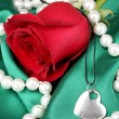 Beautiful red rose with heart pendant — Stockfoto