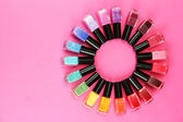 Group of bright nail polishes, on pink background — Stock Photo