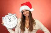 Belle jeune femme avec horloge, sur fond rouge — Photo