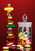 Capsules and pills hill and in receptacle on red background — Stock Photo