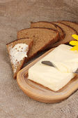 Butter on wooden holder surrounded by bread and flowers on sacking backgrou — Stock Photo