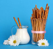 Tasty crispy sticks in glass cup on blue background — Stock Photo