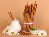 Tasty crispy sticks in glass cup on beige background — Stock Photo