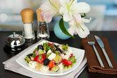 Färska grekisk sallad på vit platta på bord på restaurang bakgrund — Stockfoto
