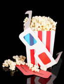 Popcorn with glasses and tickets isolated on black — Stock Photo