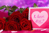 Beautiful bouquet of roses with valentine on pink fabric on purple backgrou — Stock Photo