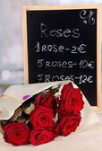 Wonderful bouquet of red roses with tablet on their selling — Stock Photo