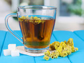 šálek čaje s slaměnka na modré dřevěný stůl na pozadí okna — Stock fotografie