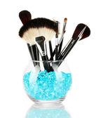 Make-up brushes in a bowl with stones isolated on white — Stock Photo