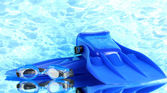 Blue flippers and goggles on blue sea background — Stock Photo