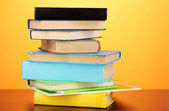 Stack of interesting books and magazines on wooden table on orange backgrou — Stock Photo