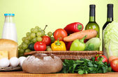 Composition with vegetables in wicker basket on green background — Stock Photo