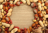 Assortment of tasty nuts on wooden background — Stock Photo