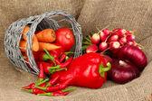 Färska röda grönsaker på säckväv bakgrund — Stockfoto