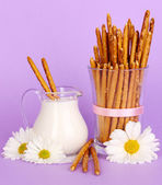 Tasty crispy sticks in glass cup on purple background — Stock Photo