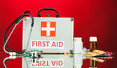 First aid box, on red background — Stock Photo