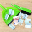 Sweeps money in the shovel on wooden background close-up - 图库照片