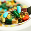 Colorful capsules and pills on plate with spoon, close up - Stock Photo