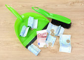 Sweeps money in the shovel on wooden background close-up — Stock Photo
