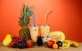 Milk shakes with fruit on red background close-up — Stock Photo
