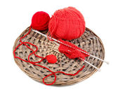 Red knittings yarns on the wicker cradle close-up isolated on white — Stock Photo