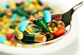 Colorful capsules and pills on plate with spoon, close up — Stock Photo