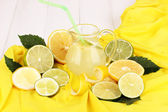 Citrus lemonade in glass pitcher of citrus around on yellow fabric on white — Stock Photo