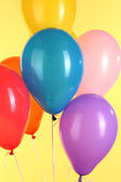Colorful balloons on yellow background — Stock Photo