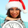 Beautiful young woman with clock, on blue background — Stock Photo #14082371