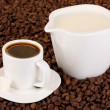 Stock Photo: A cup of strong coffee and sweet cream on coffee beans close-up