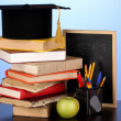 Books and magister cap against school board on wooden table on blue backgro — Stockfoto